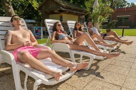 loungers: Four friends sunbathe on the sun loungers on the beach