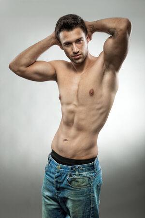 Handsome muscular man posing half naked photo