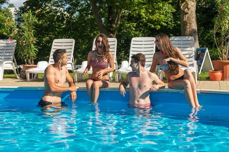 nadar: Cuatro amigos que se divierten en la piscina