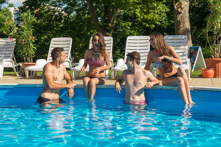 pool fun: Four friends having fun in the swimming pool