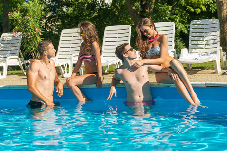 splash pool: Four friends having fun in the swimming pool