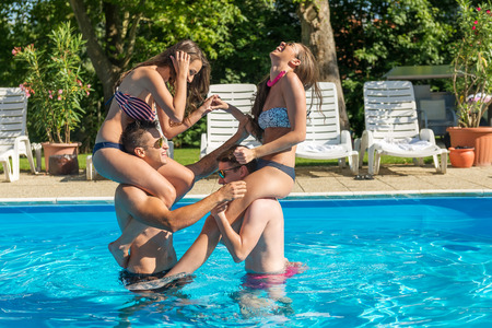 Four friends having fun in the swimming pool photo