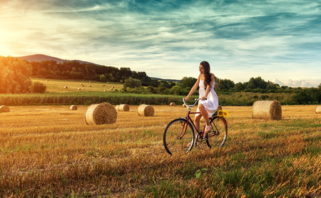 Beautiful woman cycling on an old red bike, in a wheat field