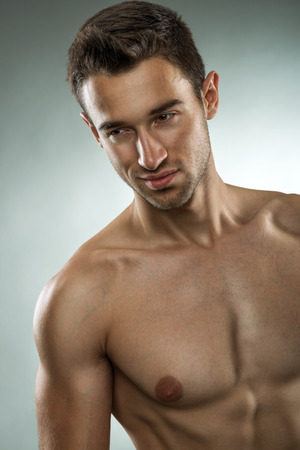 Handsome muscular man posing half naked, close-up photo photo