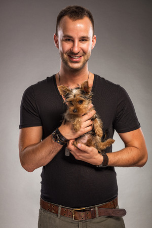 Handsome young man holding a yorkshire terrier dog photo