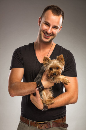 man dog: Handsome young man holding a yorkshire terrier dog
