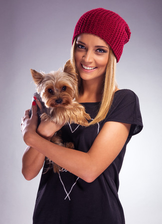 Beautiful blonde woman in autumn dress, holding a yorkshire terrier dog photo