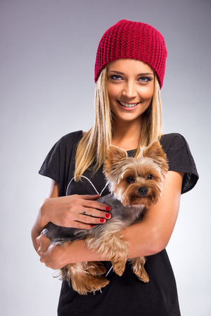 Beautiful woman with autumn fashion, holding yorkshire terrier dog photo