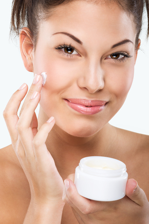Flawless-skinned woman with moisturizing face cream
