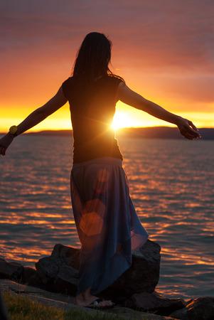 Woman enjoying the sunset at the lake photo