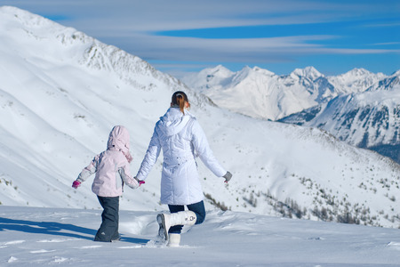 Mother and daughter walking in the mountains of the vast snow photo