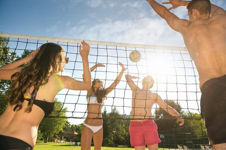 balon de voley: Amigos jugar voleibol en la playa Foto de archivo