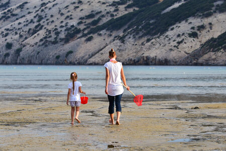 Mother and daughter be fishing nets in the sea photo