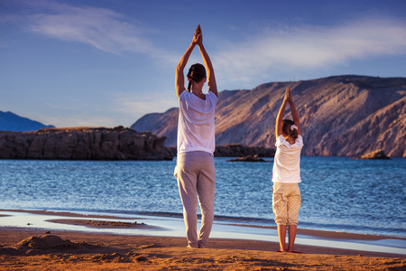 Mother and daughter, yoga on the beach early in the morning photo
