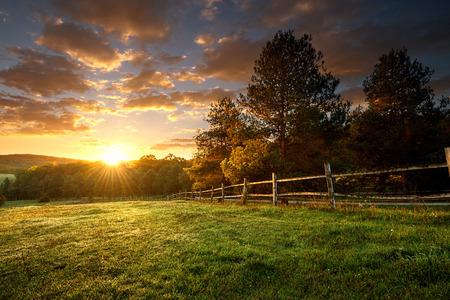 Picturesque landscape, fenced ranch at sunrise Standard-Bild