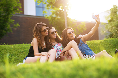 fash: Selfie Photo.three pretty woman enjoying the nice weather on the grass Stock Photo