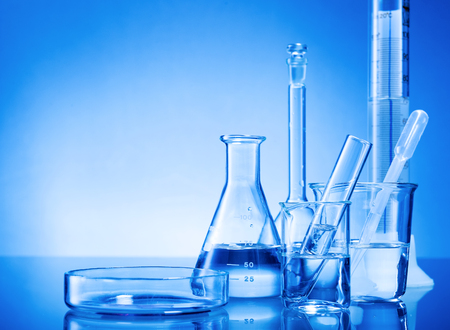 test glass: Laboratory equipment, glass flasks, pipettes on blue background Stock Photo