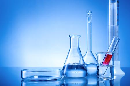 material de vidrio: Equipo de laboratorio, frascos de vidrio, pipetas, líquido rojo sobre fondo azul Foto de archivo