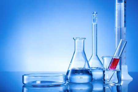 glassware: Laboratory equipment, glass flasks, pipettes, red liquid on blue background