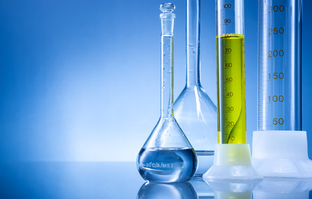 Laboratory equipment, bottles, flasks with yellow  liquid  on blue background