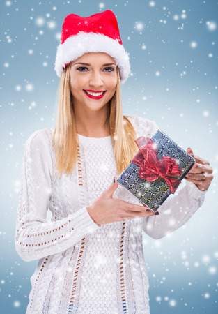 Beautiful woman with santa hat in his hand a gift photo