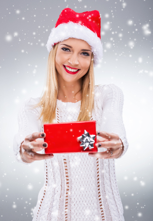 Beautiful woman with santa hat holding a small red gift box photo
