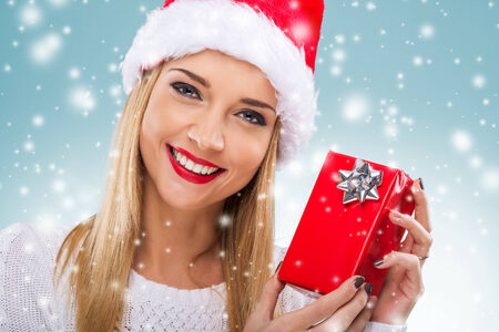 Beautiful woman with santa hat holding red gift box, close-up photo