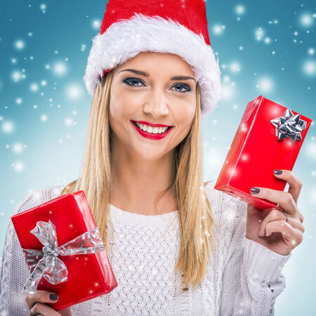 Beautiful woman with santa hat, holding two red gift box - snowfall photo