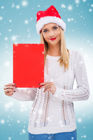 subtitles:   Beautiful woman with santa hat, holding a red paper without subtitles