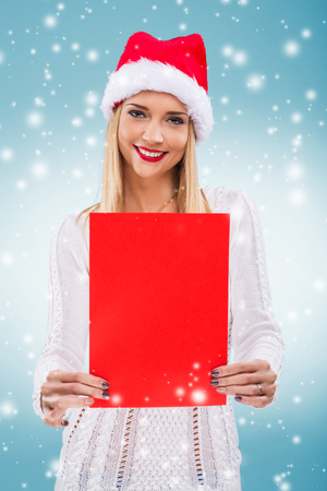 Beautiful woman with santa hat, holding a red paper without subtitles photo