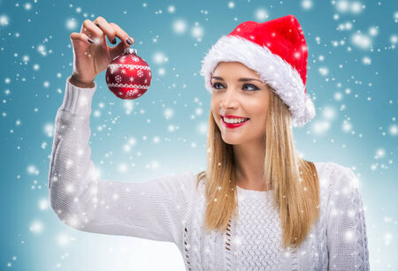 Beautiful woman with santa hat holding red Christmas Ornament photo