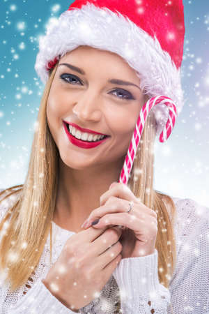 Beautiful woman with santa hat holding red -white Christmas Lollipop photo