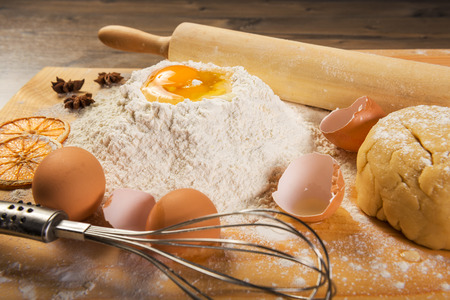 Baking preparation: eggs, flour, rolling pin, spices on a board Stock Photo