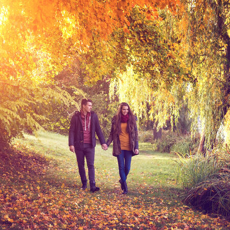 romantic sky: Couple holding hands walking in the forest in autumn Stock Photo
