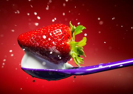 Strawberry on the purple spoon and milk splash.  photo