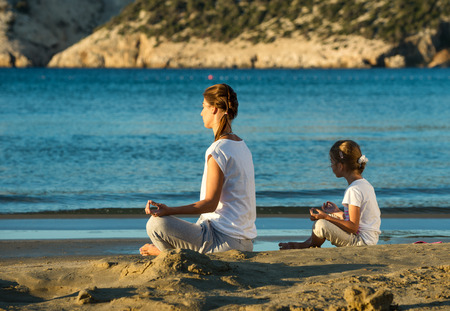 Mother and daughter doing yoga exercise on the beach photo