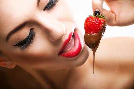 strawberry chocolate: Seduction - red female lips eating chocolate strawberries Stock Photo