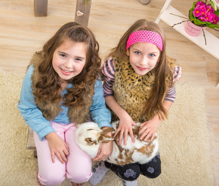 fondle: Easter - Little girls stroking the huge, live bunny Stock Photo