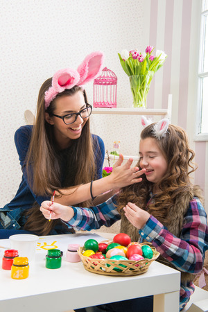 Easter - Mother and daughter paint eggs, bunny ears on them