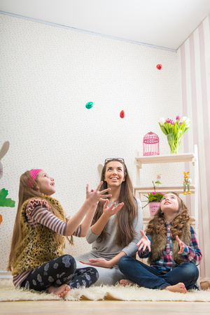 Easter - Mother and two daughters chocolate eggs thrown photo