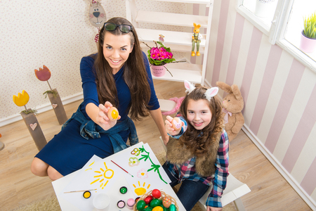 Easter - Mother and daughter paint eggs, bunny ears on them photo