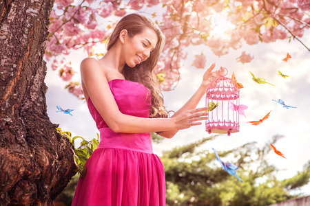 Beautiful woman  hold hands birdcage  surrounded by a lot of butterflies photo
