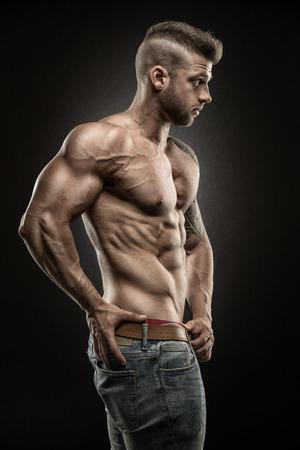 desnudo masculino: Muscular vista lateral del hombre sobre fondo negro Foto de archivo