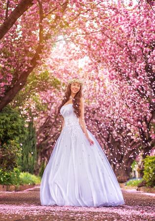 vestido blanco: Novia hermosa en un vestido blanco bajo el �rbol de sakura y p�talos de flores