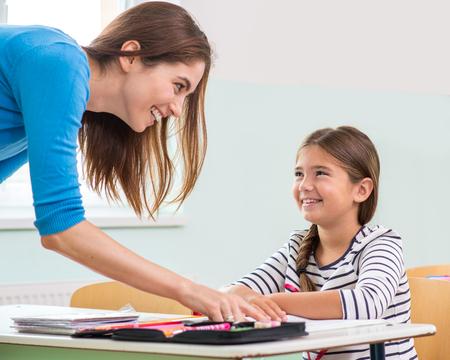 Female teacher shows the children the book, reading