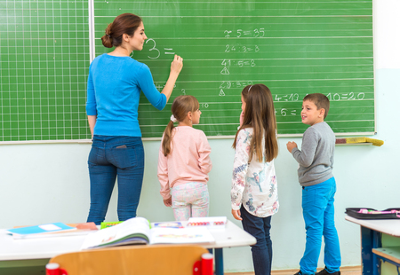 classes: Teacher and student at the blackboard, math class Stock Photo