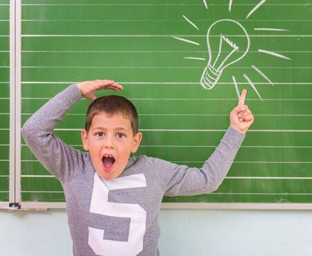 funny boy: Funny little boy showing on the board: light bulb,