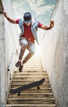boy skater: Professional skateboarder boy jumps off the stairs