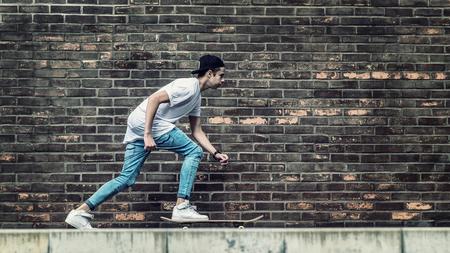 niño en patines: Chicos skater por pared de ladrillo