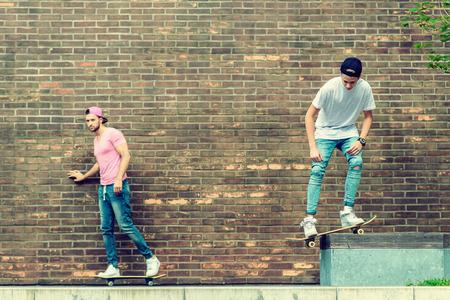 mujeres juntas: Chicos skater por pared de ladrillo